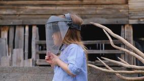 La muchacha en camisa pone un casco protector que sueña sobre la profesión futura metrajes