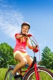 La muchacha en camisa roja se sienta en una bicicleta Fotografía de archivo
