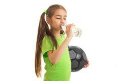La muchacha en camisa verde con el balón de fútbol en manos bebe el agua Imagenes de archivo