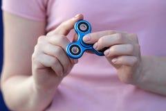 La muchacha en camiseta rosada está jugando al hilandero azul del metal en las manos en la calle, mujer que juega con un juguete  Imagenes de archivo