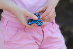 La muchacha en camiseta rosada está jugando al hilandero azul del metal en las manos en la calle, mujer que juega con un juguete  Foto de archivo