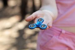 La muchacha en camiseta rosada está jugando al hilandero azul del metal en las manos en la calle, mujer que juega con un juguete  Fotos de archivo