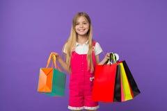 La muchacha en cara sonriente lleva los manojos de panieres, aislados en el fondo blanco La muchacha le gusta comprar de moda Fotos de archivo