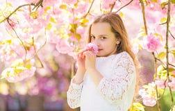 La muchacha en la cara sonriente que se coloca cerca de Sakura florece, defocused Concepto del perfume y de la fragancia Muchacha imágenes de archivo libres de regalías