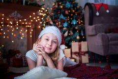 La muchacha en casquillo de la Navidad miente en el fondo de la chimenea y del árbol de navidad brillantes Imágenes de archivo libres de regalías