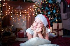 La muchacha en casquillo de la Navidad miente en el fondo de la chimenea y del árbol de navidad brillantes Fotos de archivo libres de regalías