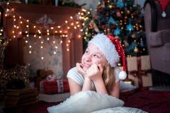 La muchacha en casquillo de la Navidad miente en el fondo de la chimenea y del árbol de navidad brillantes Foto de archivo libre de regalías