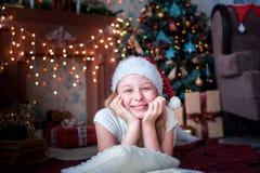 La muchacha en casquillo de la Navidad miente en el fondo de la chimenea y del árbol de navidad brillantes Imagen de archivo