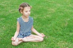La muchacha en chaleco rayado se sienta en loto Foto de archivo