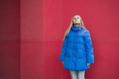 La muchacha en chaqueta azul se coloca en el fondo de una pared rosada Fotos de archivo libres de regalías