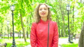 La muchacha en la chaqueta de cuero roja que mira la cámara y aprobada algo por sacudidas dirige metrajes