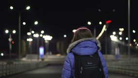 La muchacha en la chaqueta del invierno camina el baile en la ciudad de la noche, la ubicación de Sochi, Rusia metrajes