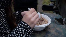La muchacha en la chaqueta está comiendo el cereal de un cuenco plástico cocinado en la cocina del campo de un soldado Consumici? almacen de video