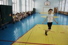 La muchacha en clase de la gimnasia en la escuela Imágenes de archivo libres de regalías