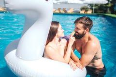 La muchacha en colchón de aire está nadando en piscina con el novio Ella toca su nariz El individuo mira la mujer joven y el guiñ imagenes de archivo