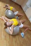 La muchacha en cortocircuitos ejercita en bola grande en gimnasia Foto de archivo