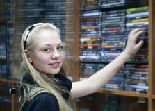 La muchacha en departamento elige el disco Foto de archivo