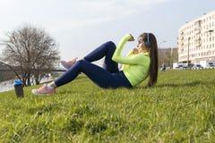 La muchacha en deportes verdes remata enganchado a fintess en el césped en la ciudad al aire libre, muchacha sacude la prensa fotos de archivo