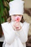 La muchacha en doctor viste con un estetoscopio en las manos de Foto de archivo libre de regalías