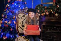 La muchacha en el árbol de navidad con un regalo en manos Foto de archivo libre de regalías