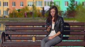 La muchacha en el banco con el teléfono No puede conseguir a través, enojado S almacen de video