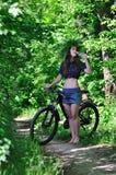 La muchacha en el bosque en un agua potable de la bici Foto de archivo