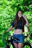 La muchacha en el bosque en un agua potable de la bici Imagen de archivo