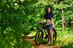 La muchacha en el bosque en una bici Imágenes de archivo libres de regalías
