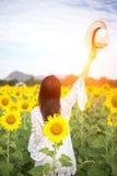 La muchacha en el campo de girasoles, así que felices hermosos y se relajan Imágenes de archivo libres de regalías