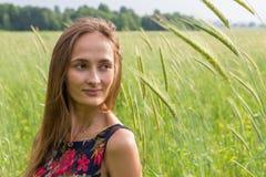 La muchacha en el campo mira en la distancia Foto de archivo libre de regalías