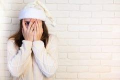 La muchacha en el casquillo de la Navidad cubrió su cara La pared blanca Fotos de archivo libres de regalías