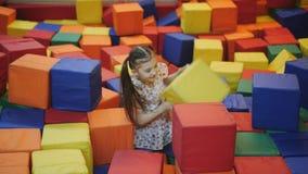 La muchacha en el centro del trampol?n est? construyendo un castillo en cubos multicolores suaves metrajes
