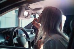 La muchacha en el coche pinta los labios Foto de archivo