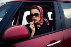 La muchacha en el coche pinta sus labios Imagenes de archivo