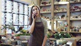 La muchacha en el delantal que habla por el teléfono metrajes