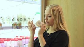 La muchacha en el departamento de la lechería elige la leche metrajes