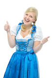 La muchacha en el dirndl más oktoberfest muestra los pulgares para arriba Imagen de archivo libre de regalías