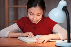 Muchacha en el escritorio que lee un libro por la luz de la lámpara Foto de archivo libre de regalías