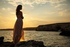La muchacha en el fondo de un paisaje marino y de una puesta del sol hermosos, silueta de una muchacha en un acantilado, en un ac Imagenes de archivo