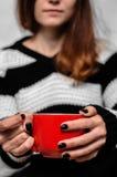 La muchacha en el fondo, sosteniendo una taza roja de té Foto de archivo libre de regalías