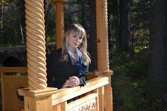 La muchacha en el gazero de madera Imagen de archivo