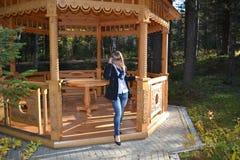 La muchacha en el gazero de madera hacia fuera fotos de archivo