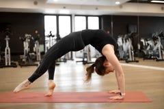 La muchacha en el gimnasio hace yoga para mantenerse forma o exceso de peso del control imágenes de archivo libres de regalías