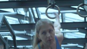 La muchacha en el gimnasio, levanta pesos del metal y fruncir el ce?o con esfuerzo almacen de metraje de vídeo