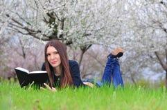 La muchacha en el jardín florecido miente en la hierba y a de la lectura Imagenes de archivo