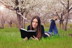 La muchacha en el jardín florecido miente en la hierba y a de la lectura Fotografía de archivo libre de regalías