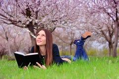 La muchacha en el jardín florecido miente en la hierba y a de la lectura Imagen de archivo libre de regalías