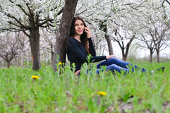 La muchacha en el jardín florecido que habla en el teléfono Foto de archivo libre de regalías