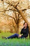 La muchacha en el jardín florecido que habla en el teléfono Fotografía de archivo libre de regalías