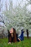 La muchacha en el jardín florecido que miente en la hierba Foto de archivo libre de regalías